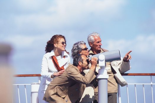 2 couples laughing and joking, looking through telescope alongside railings on deck Mont St Michel ©Brittany Ferries