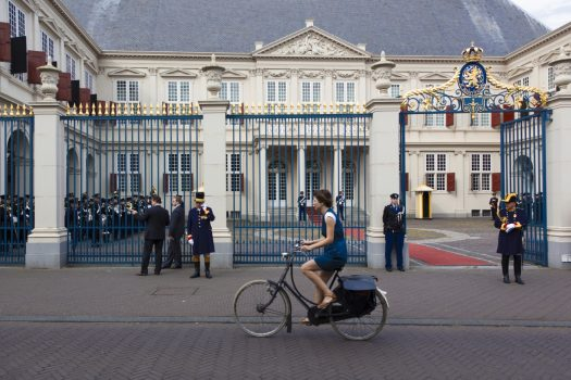 Historical holland dutch royal palaces and gardens girl cycling past the noordeinde palace in the hague holland nbtc publicscrutiny Choice Image